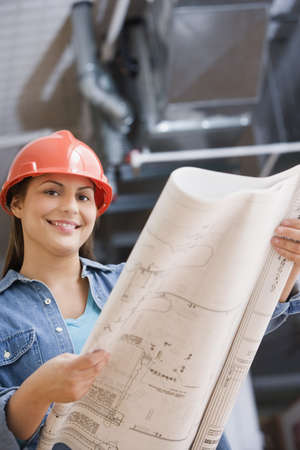 female construction worker: Hispanic female construction worker looking at blue prints