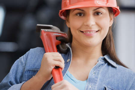 female construction worker: Hispanic female construction worker holding a wrench