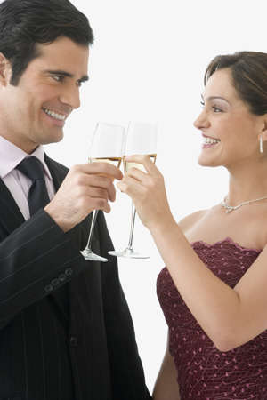 wooing: Studio shot of couple toasting with champagne glasses LANG_EVOIMAGES