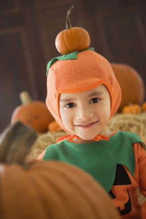 finding a mate: Young Hispanic child in pumpkin costume with pumpkins LANG_EVOIMAGES