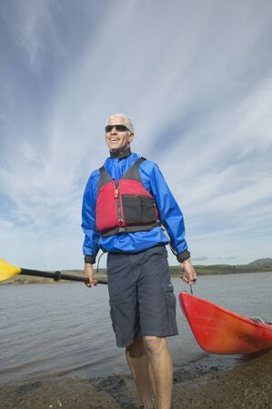 Middle-aged man pulling kayak out of the water, California, United States