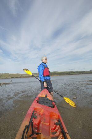 tugging: Middle-aged man holding kayak and paddle, California, United States