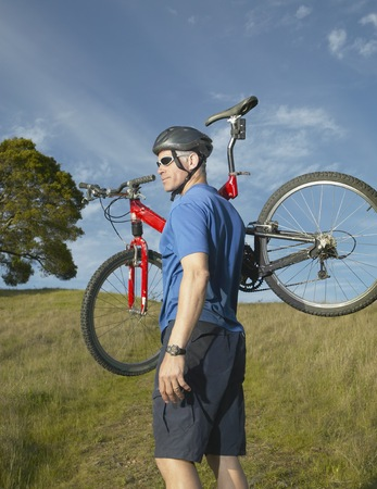 middleaged: Middle-aged man carrying bicycle in the countryside, California, United States
