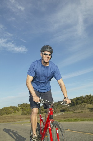 tugging: Middle-aged man riding a bicycle on a rural road, California, United States