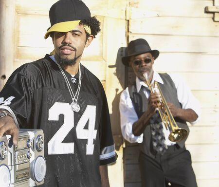 boom box: Young African man with boom box next to senior African man with trumpet, Oakland, California, United States