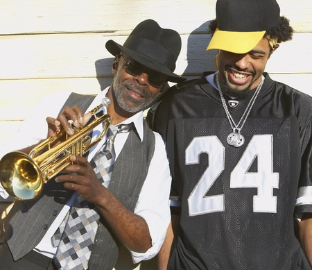 fathering: Young African man laughing next to senior African man with trumpet, Oakland, California, United States