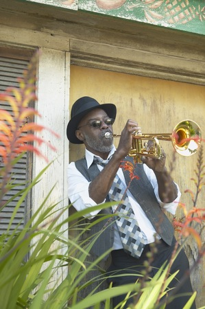 Senior African man playing the trumpet while leaning in a doorway, Oakland, California, United States