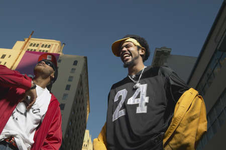seriousness skill: Low angle view of two young African men standing in urban area, Oakland, California, United States