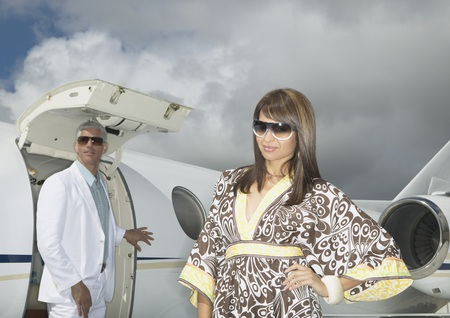 approaching: Couple standing in front of small jet, Nobato, California, United States LANG_EVOIMAGES