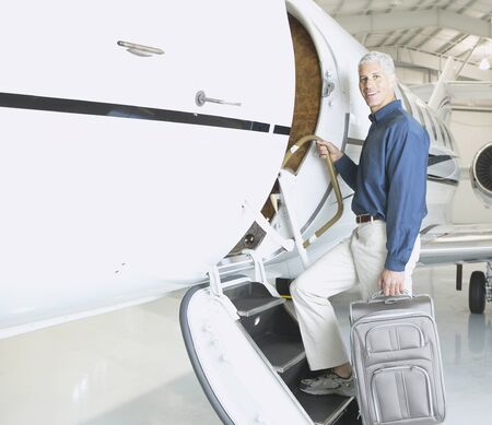 ostentatious: Man with suitcase boarding airplane in hanger, Nobato, California, United States LANG_EVOIMAGES