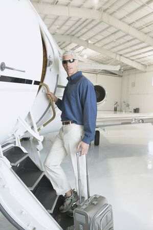 approaching: Man with suitcase boarding airplane in hanger, Nobato, California, United States LANG_EVOIMAGES