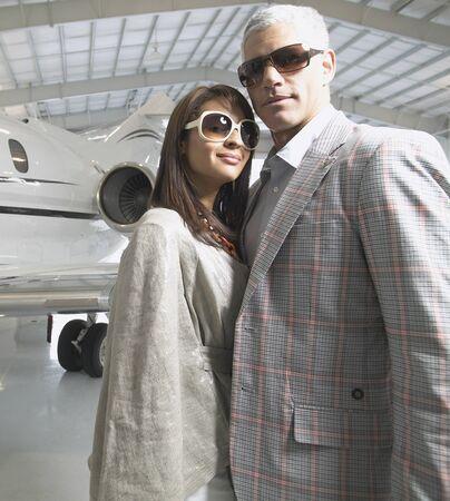 Couple standing next to airplane in hanger, Nobato, California, United States Imagens