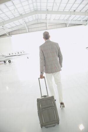 go inside: Man with suitcase walking out of airplane hanger, Nobato, California, United States