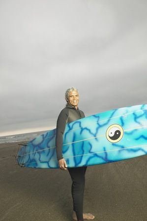 adventuresome: Senior male surfer carrying his surfboard on the beach, Oakland, California, United States LANG_EVOIMAGES
