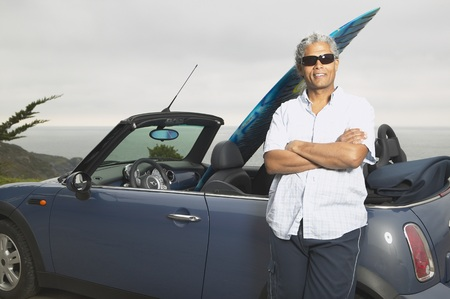 casualness: Senior man leaning on a convertible with a surfboard in it, Oakland, California, United States