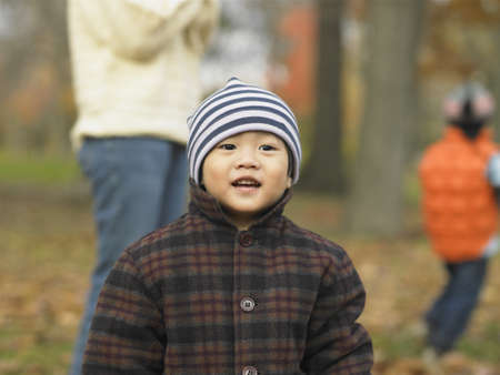 Young Asian child in hat and coat at the park, Toronto, Canada