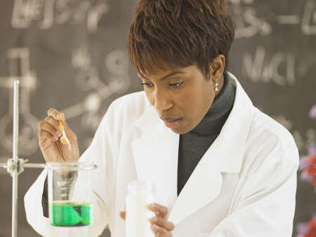 conducting: African female science teacher conducting experiment