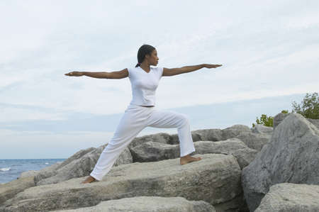 motioning: African woman stretching on rocks at the beach