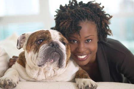 cherishing: Young African woman smiling with British Bulldog