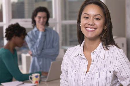 north western european descent: Hispanic businesswoman with co-workers in the background