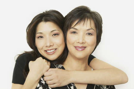 30s adult: Studio shot of Asian mother and adult daughter hugging LANG_EVOIMAGES