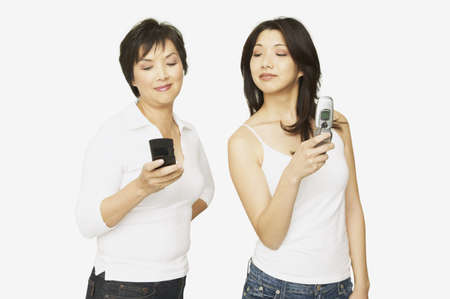 acknowledging: Studio shot of Asian mother and adult daughter with cell phones