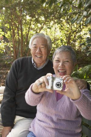 san rafael: Senior Asian couple sitting on a park bench with a digital camera, San Rafael, California, United States