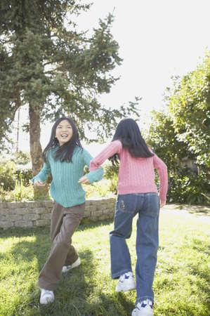san rafael: Two young Asian sisters playing outdoors, San Rafael, California, United States LANG_EVOIMAGES