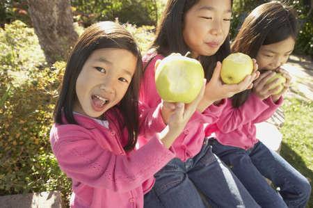 san rafael: Three young Asian sisters eating green apples, San Rafael, California, United States