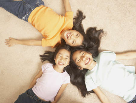 delighted: Three young Asian sisters lying on the floor with their heads together, San Rafael, California, United States