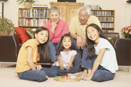 playing on divan: Three young Asian sisters playing chinese checkers while grandparents watch, San Rafael, California, United States