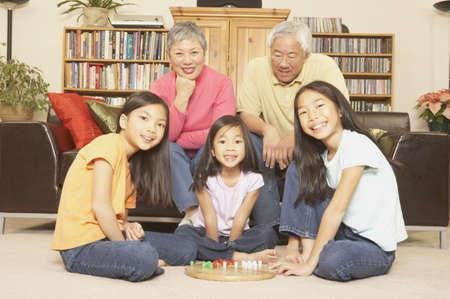 san rafael: Three young Asian sisters playing chinese checkers while grandparents watch, San Rafael, California, United States