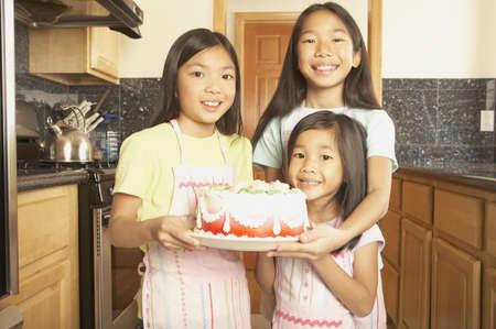 san rafael: Three young Asian sisters holding a cake in the kitchen, San Rafael, California, United States