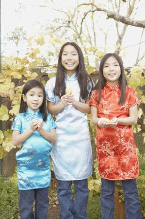 san rafael: Three young Asian sisters holding fortune cookies, San Rafael, California, United States