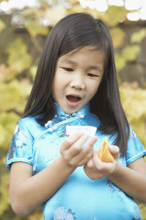 san rafael: Young Asian girl holding a fortune cookie and reading her fortune, San Rafael, California, United States LANG_EVOIMAGES