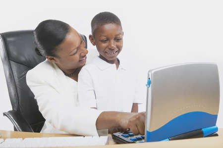 computer instruction: African businesswoman teaching her young son on a computer, San Rafael, California, United States