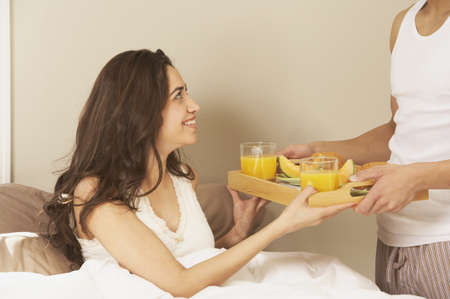 Hispanische Frau, die im Bett frühstücken, San Rafael, Kalifornien, USA