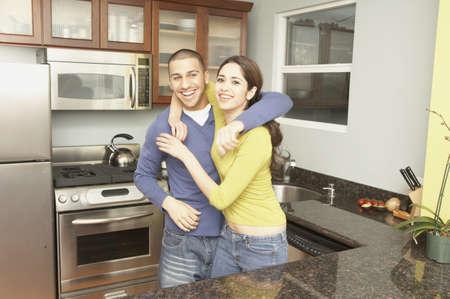 san rafael: Young Hispanic couple hugging in the kitchen, San Rafael, California, United States