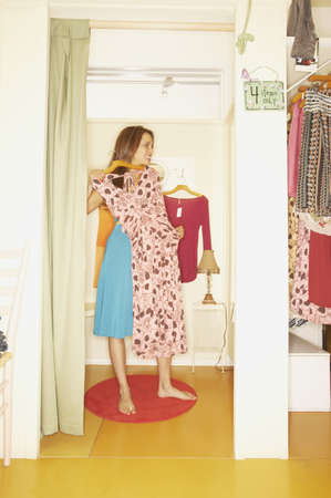 fitting room: Woman holding up a dress in a fitting room, Larkspur, California, United States