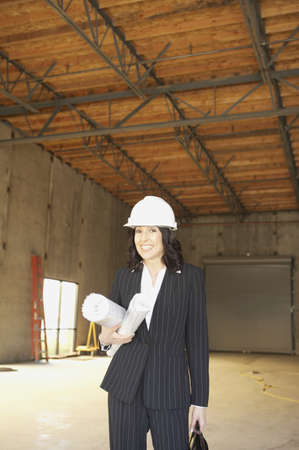 front raise: Businesswoman standing in empty warehouse with blueprints, San Rafael, California, United States