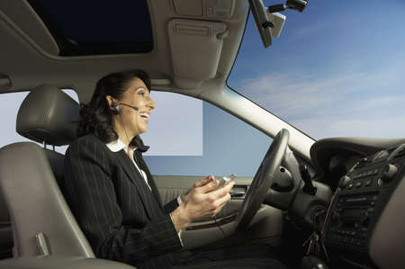 car side view: Businesswoman driving and talking on a headset, San Rafael, California, United States LANG_EVOIMAGES