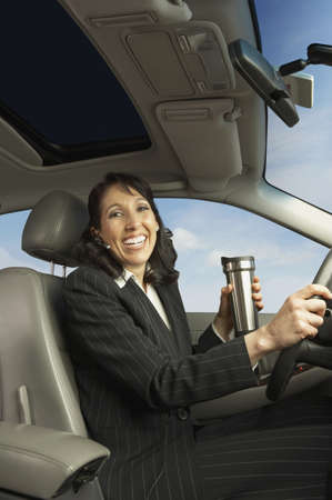 san rafael: Businesswoman driving with travel mug, San Rafael, California, United States