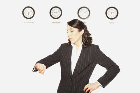 telecommuter: Businesswoman checking her watch in front of clocks with different time zones, San Rafael, California, United States