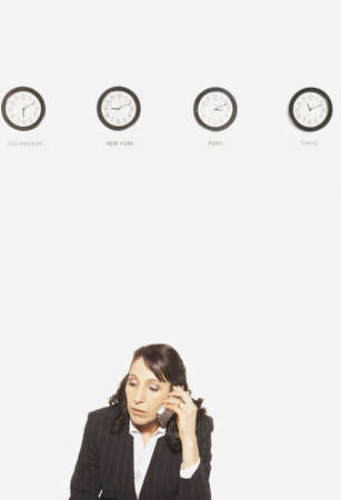 san rafael: Businesswoman in front of clocks with different time zones, San Rafael, California, United States LANG_EVOIMAGES
