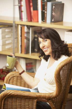 san rafael: Woman sitting reading and drinking tea, San Rafael, California, United States
