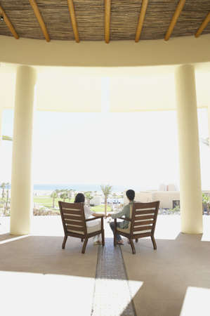 longshot: Couple sitting in deck chairs at hotel, Los Cabos, Mexico LANG_EVOIMAGES