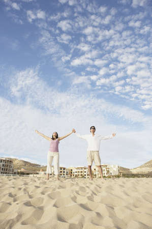los cabos: Couple standing on beach with arms outstretched, Los Cabos, Mexico