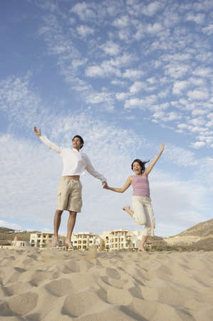los cabos: Couple jumping on beach, Los Cabos, Mexico LANG_EVOIMAGES