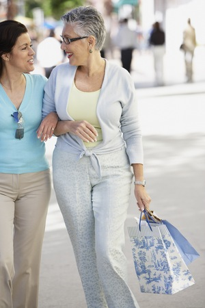 stepping: Two middle-aged woman walking arm in arm, Miami, Florida, United States LANG_EVOIMAGES