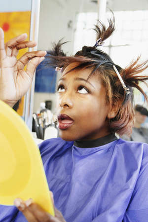 dubious: Young woman checking her hair in beauty salon